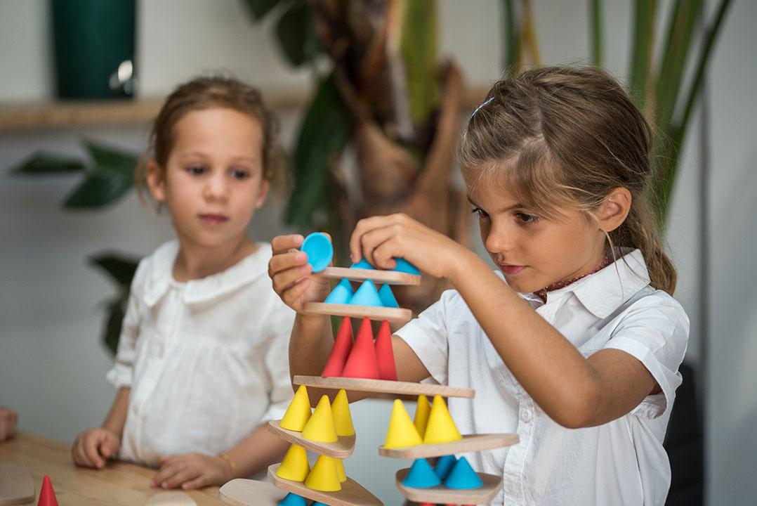 Deux enfants jouants ensemble à Piks en pleine concentration illustrant l'importance du design pour l'éducation